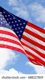 Close up isolated colorful United states of American U.S. flag with stars and stripes red white and blue against a blue sky with puffy white clouds