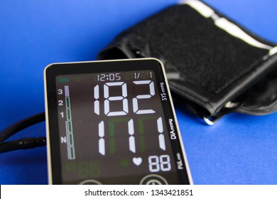 Close up of isolated digital monitor gauge with cuff showing high diastolic and systolic blood pressure
