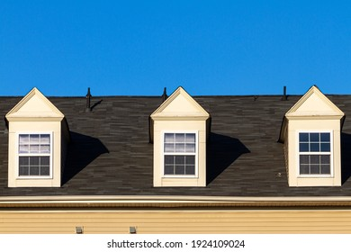 Close up isolated image of three false dormer windows (gabbled style) on a shingles covered roof at a modern house. These features are nonfunctional but have cosmetic and decorative purposes in USA.
