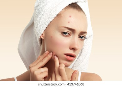 Close up isolated portrait of young woman squeezing pimple on her cheek in the bathroom. Cropped view of Caucasian female having skin problem, against blue wall background. Beauty and spa concept