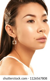 Close up isolated studio portrait of a young Asian lady with nude make-up. The beautiful brunette girl wearing delicate square-shaped earrings, posing on the white background, looking to the side.
