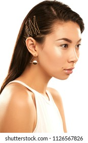 Close up isolated studio portrait of a young Asian lady with nude make-up. The side view of the girl wearing delicate golden geometric earrings, posing on the white background, looking straight ahead.