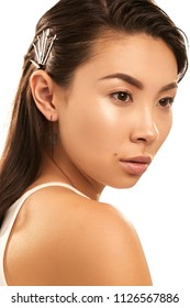 Close up isolated studio portrait of a young Asian lady with nude make-up. The brunette girl with sleek hairstyle, bobby pins in her hair, posing against the white background, looking to the side.