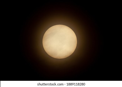 Close up isolated telephoto image of the sun in the sky taken using a super telephoto lens and a Natural Density Filter. Clouds are  seen in front of it.