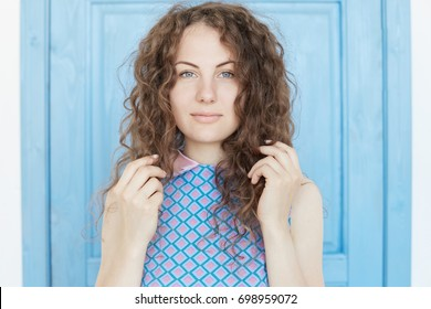 Close up isolated view of beautiful young brunette woman with perfect healthy skin and blue eyes, looking straight with thoughtful seductive face expression, touching curly hair, blue background.