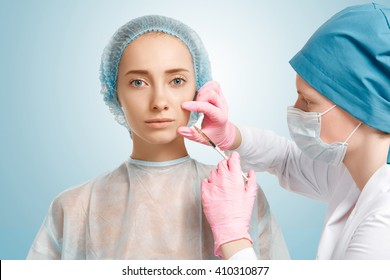 Close up isolated view of doctor in sterile gloves making Botox facial injection in woman's cheek. Young Caucasian female having treatment cosmetic in beauty clinic. Aesthetic medicine, cosmetology