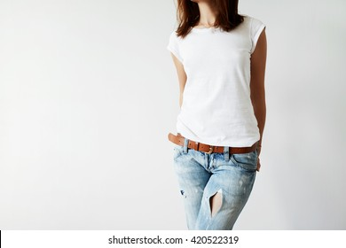 Close up isolated view of young female with dark hair in white T-shirt with copy space for your information or advertising content. Woman freelancer in casual clothes holding hands behind her back