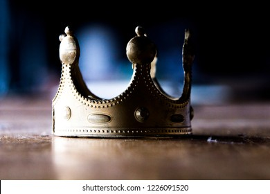Close up of an isolated  worn out plastic gold-colored  crown which lies on a worn out wooden table with a blue background 2. Slight shinier.