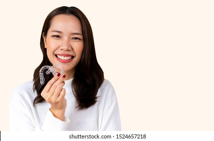 close up (isolated) young beautiful asian woman smiling with hand holding dental aligner retainer (invisible) on cream background of dental clinic for beautiful teeth treatment course concept