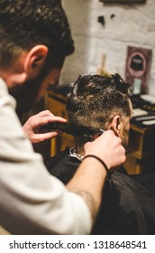 A close up of an Italian barber cutting man's hair