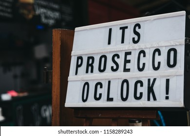 "Close up of ""It's prosecco o'clock"" black and white sign."