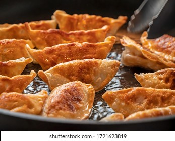 Close up of Japanese dumplings. The Gyoza dumplings cook in a pan of hot oil and are turned over to see the golden brown outer side.