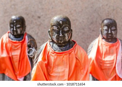 Close up of Japanese monk stone statue with orange fabric tag