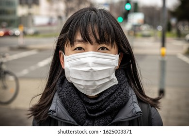 Close up of Japanese woman using medical mask in street, urban background