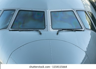 Close up of a jet airplane cockpit Front view of the airplane window with windshield wipers.