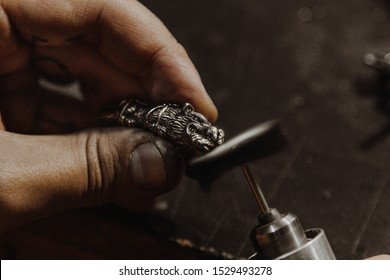 Close up of jeweler polishing a wolf shape pendant