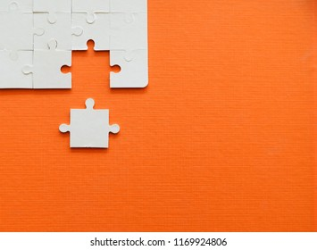 Close up jigsaw puzzle pieces on orange background,Business success concept.