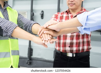 Close up join hand. Unity sign. Stacking hands of man with container background. Engineer wearing green safety vest. Real estate construction, industrial, teamwork, business concept