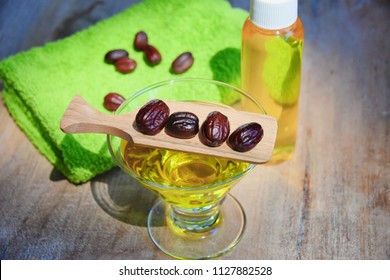 Close up of jojoba seed and oil in a glass tray on a light wood surface table. Green towel. Great for skin and hair health.