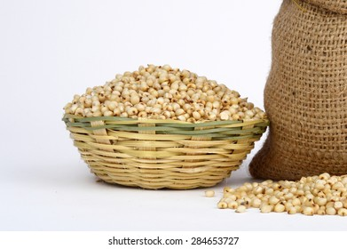 close up of Jowar (Sorghum) in wooden basket with heap and small sack.