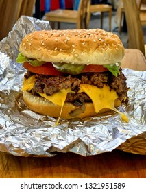 Close up of juicy cheeseburger in burger joint, unwrapped hamburger on foil on restaurant table in USA, American fast food, patty with melting cheese and salad