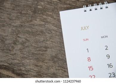 Close up July calendar on wood texture.