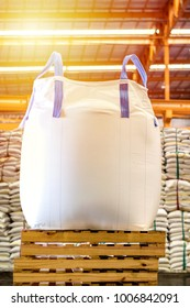 Close up of a jumbo sugar bag on wooden crates with background of bulk sugar bags.