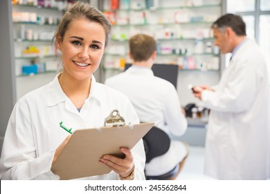 Close up of junior pharmacist writing on clipboard at the hospital pharmacy