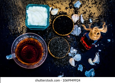 Close up of kalonji with curd or youghurt on wooden surface with black tea and its extracted oil and some garlic cloves reduces chances of cancer, ulcers and diabetes.