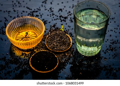 Close up of kalonji or roman coriander with water and honey on wooden surface beneficial for diabetes patient, good in losing weight.