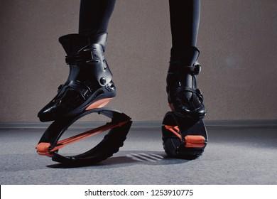 Close up kangoo shoes. beautiful and sport girl in the gym training. Kangoo jumping. Beautiful girls in Kangoo Jumping training in the gym