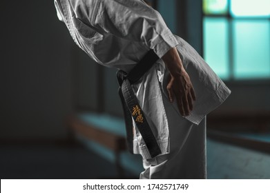 """Close Up Karate girl with black belt displaying respect - on belt Kaishin wich means """"Open Mind"""""""