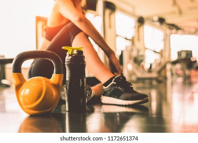 Close up kettlebells with woman exercise workout in gym fitness breaking relax after sport training with protein shake bottle background. Healthy lifestyle bodybuilding and athlete muscles dumbbells.