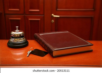 Close up of key, book and bell on wooden reception desk. Selection focus, focus on the bell.
