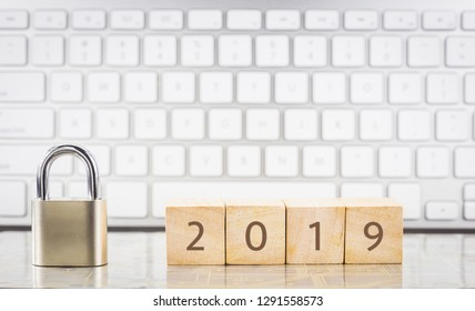 Close keypad lock with year number for 2019 on wooden cubes, white keyboard on background. New year's resolution, goal setting, business planning, database management concepts.