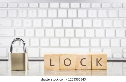 Close keypad with word LOCK on wooden cubes, white keyboard on background. Encryption, internet connection, cyber security, system login, information privacy, database management concepts.