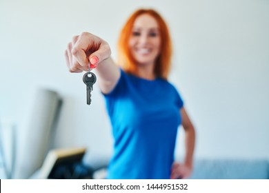 Close up of keys to new apartment with young woman in background