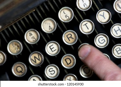 Close up of keys of vintage typewriter with finger in blurred motion