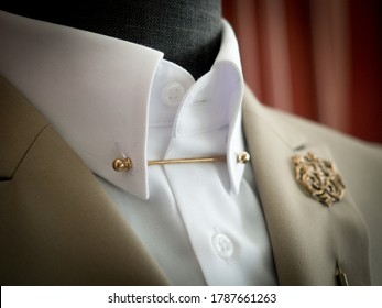 Close up of khaki tailor suit jacket detail with Lapel pin