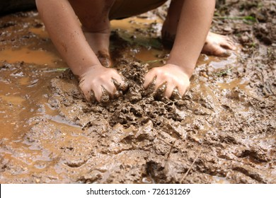 Close up of kid playing in muddy puddles. Dirty hands and legs