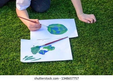 Close up kids hand drawing a picture of earth globe.Child painting with brush and acrylic color a picture of earth. Earth day, plastic free and zero waste concept.