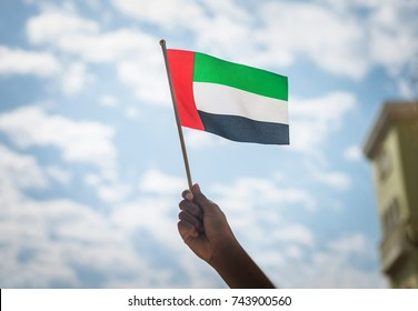 Close up of a kid's hand holding tiny flag of UAE. National day celebration by people of United Arab Emirates