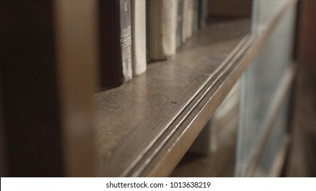 Close up of kid's hand wiping a dust on the bookshelf. Child clean up the shelf. Boy's hand clean up the bookshelf. Wiping the dust. Top view of kid cleaning the bookshelf and wiping dust