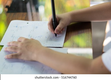Close up kid's hand writing on paper, writing messy math on wooden table in room,student child girl holding pen doing homework at home, calculate the results on paper , education concept