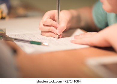 Close up kid's hand writing on paper, writing messy math on wooden table in room,student child girl holding pen doing homework at home, education concept.