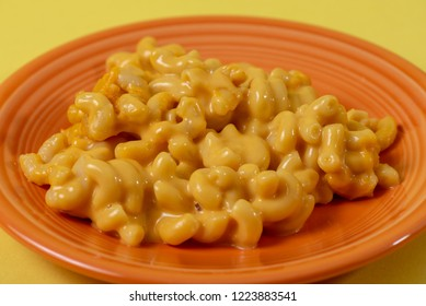 Close up of kid's style macaroni and cheese on an orange plate with a yellow background.