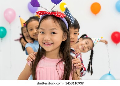 Close up of kindergarten kids or pre-teen friend smiling having fun to camera while celebration party in modern room. Birthday or Childhood, holidays, friendship concept