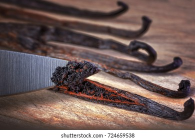 Close up of knife cutting vanilla beans seed pods on wooden background