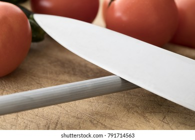 Close up of knife on honing steel with vegetables in background