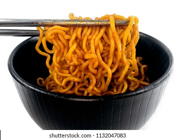 Close up Korean hot and spicy instant dry noodle in black  bowl toped with fish ball sliced meat and white background, Homemade delicious asian food concept.